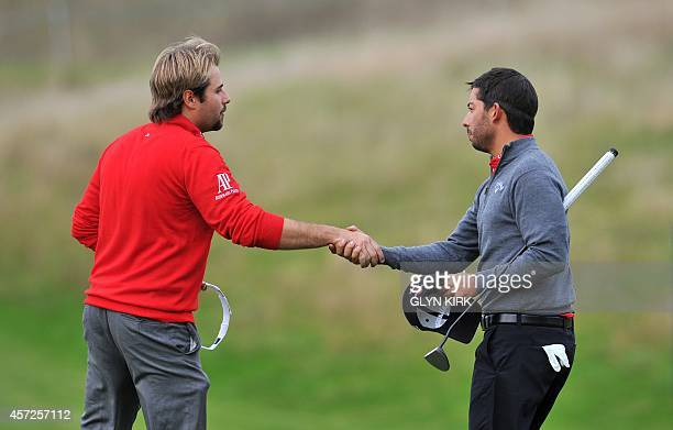 French golfer Victor Dubuisson shakes hands with Spanish golfer Pablo Larrazabal after winning 32 on the 16th green during the first day of the group...