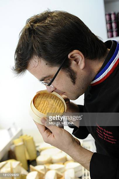 French gourmet food company Fauchon's cheese seller Francois Robin smells an Appellation d'origine protegee Epoisses cheese at a shop of Fauchon on...