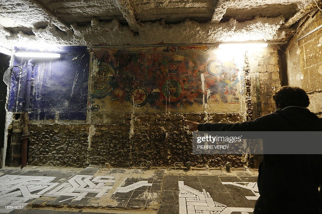 French graffiti artist Sowat (R) gestures in front of his artworks during street art performances on March 18, 2013 at the 'Bains-Douches' nightclub in Paris. Famous Parisian nightclub the 'Bains-Douches' was turned into a temporary artistic residence exhibiting street art works before revamp in early April to be turned into a hotel lounge by 2014.