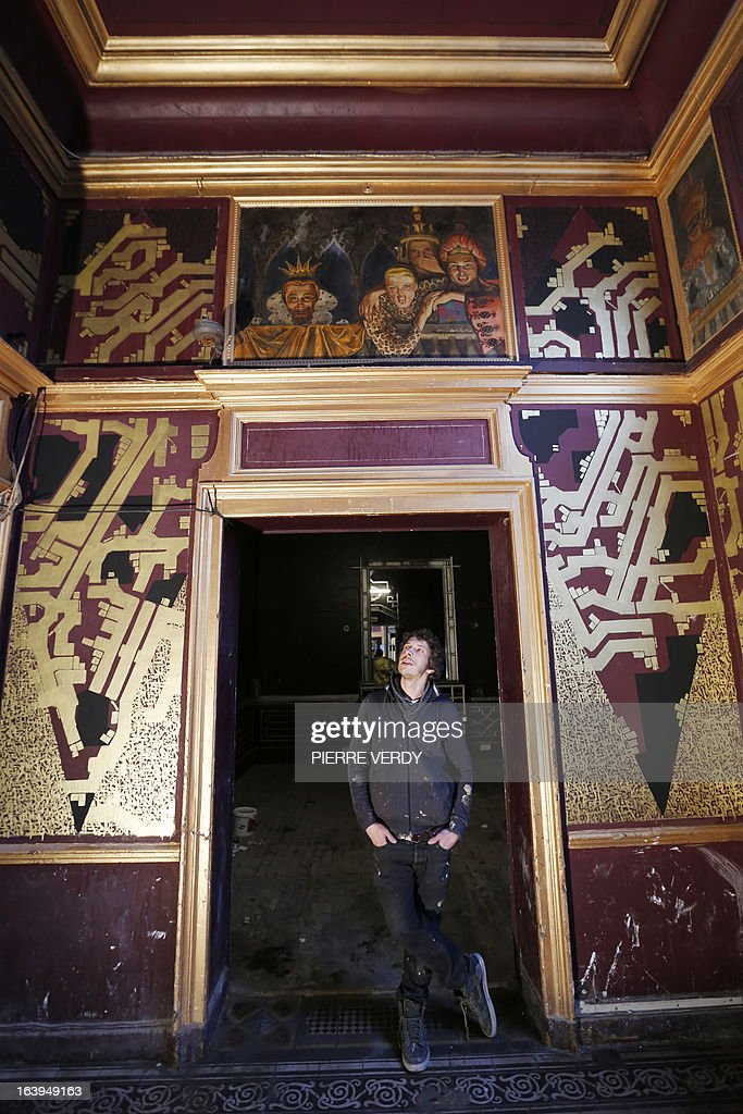 French graffiti artist Sowat poses in front of his artworks during street art performances on March 18, 2013 at the 'Bains-Douches' nightclub in Paris. Famous Parisian nightclub the 'Bains-Douches' was turned into a temporary artistic residence exhibiting street art works before revamp in early April.