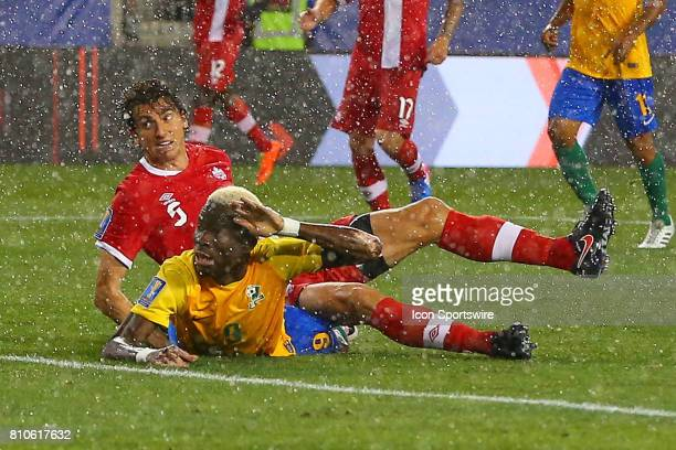 French Guiana forward Arnold Abelenti battles for the ball during a down pour Canadian National Soccer Team defender Dejan Jakovic during the second...