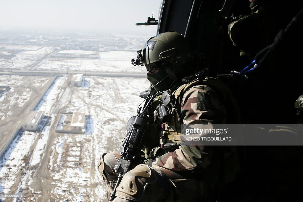 A French gunner (L) sits in a military helicopter flying above Kabul on January 01, 2013. AFP PHOTO KENZO TRIBOUILLARD