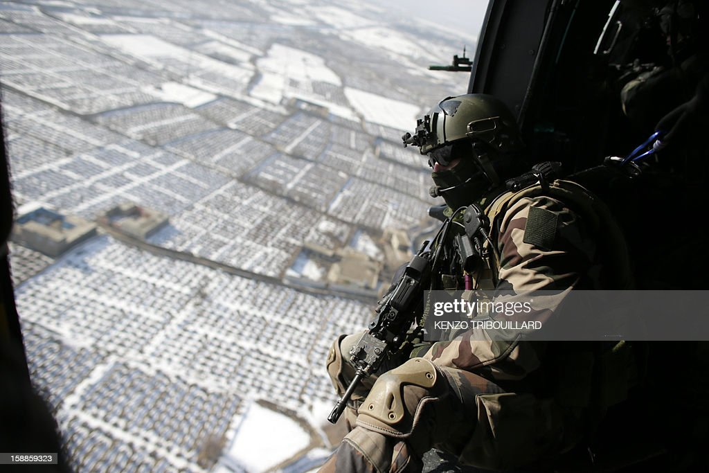 A French gunner (L) sits in a military helicopter flying above Kabul on January 01, 2013.