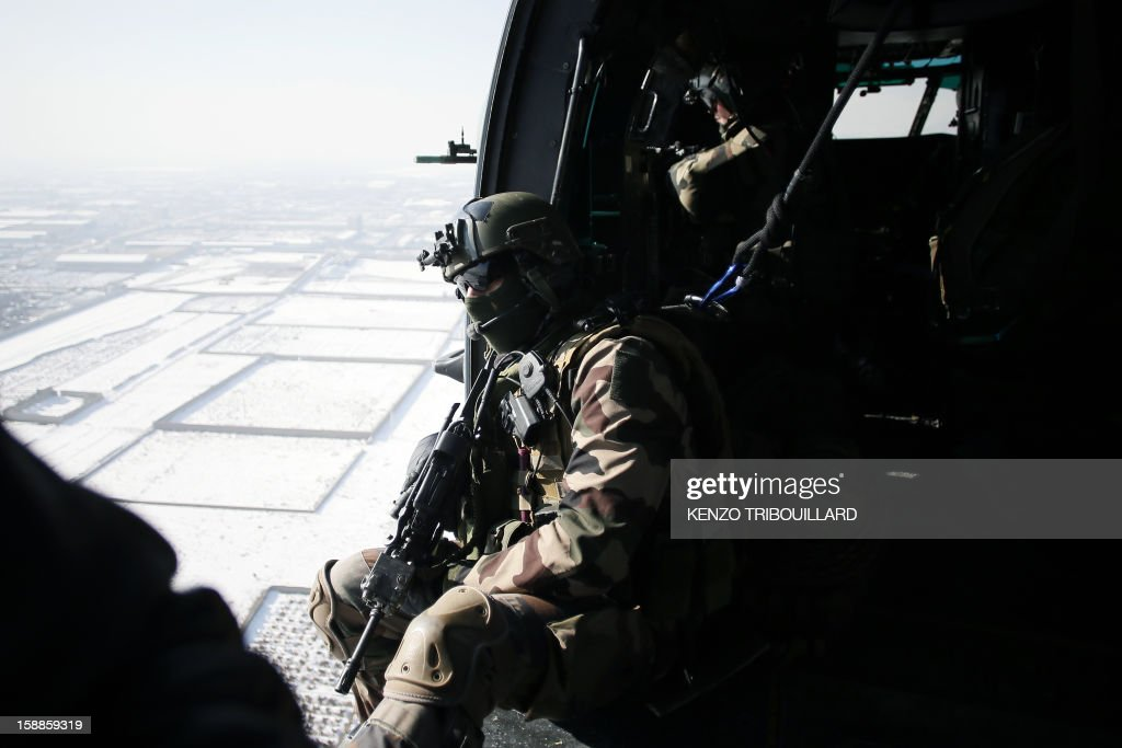 French gunners sit in a military helicopter flying above Kabul on January 01, 2013.