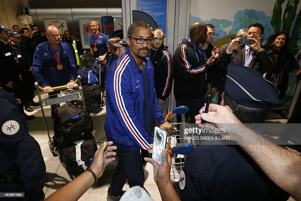 French handball national team deputy coach, <a gi-track='captionPersonalityLinkClicked' href=/galleries/search?phrase=Didier+Dinart&family=editorial&specificpeople=710241 ng-click='$event.stopPropagation()'>Didier Dinart</a> (C), is welcomed by supporters on February 2, 2015 at the Roissy Charles de Gaulle Airport in Roissy-en-France, outside Paris, upon the arrival of the team from Qatar, after winning the 24th Men's Handball World Championships. France became the first team in handball history to win five world championships when they beat surprise finalists Qatar 25-22 on February 1, 2015. The win means France's are now world, European and Olympic champions, emphasising their current dominance of the sport.