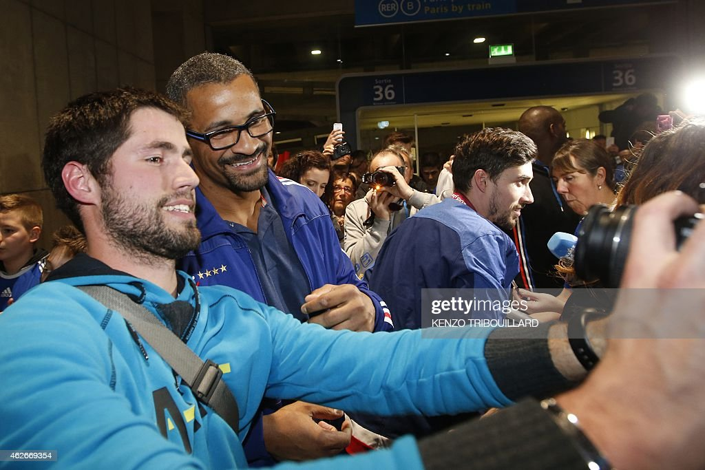 French handball national team deputy coach, <a gi-track='captionPersonalityLinkClicked' href=/galleries/search?phrase=Didier+Dinart&family=editorial&specificpeople=710241 ng-click='$event.stopPropagation()'>Didier Dinart</a> (2ndL) poses for a selfie picture with a supporter, on February 2, 2015 at the Roissy Charles de Gaulle Airport in Roissy-en-France, outside Paris, upon the arrival of the team from Qatar, after winning the 24th Men's Handball World Championships. France became the first team in handball history to win five world championships when they beat surprise finalists Qatar 25-22 on February 1, 2015. The win means France's are now world, European and Olympic champions, emphasising their current dominance of the sport.