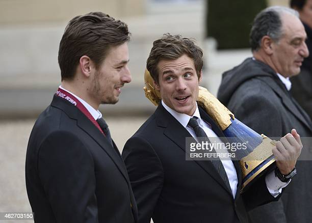 French handball national team players Xavier Barachet and Kentin Mahe holding the team's IHF world champion trophy leave the Elysee presidential...