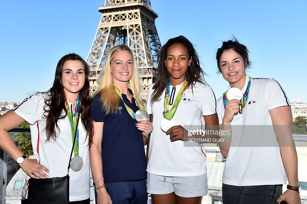 French handball players Marie Prouvensier Manon Houette Estelle Nze Minko and Chloe Bulleux pose with their silver medals on August 23 in front of...