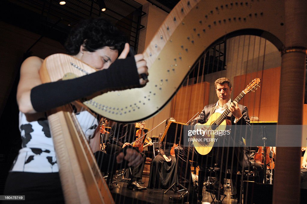 French harpist Isabelle Moretti (L) and guitarist Emmanuel Rossfelder get ready prior to a concert with Yokohama Sinfonietta as part of the 'Folle Journee' classic music festival on February 1, 2013 in Nantes. The 19th edition of this festival will run until next February 3.
