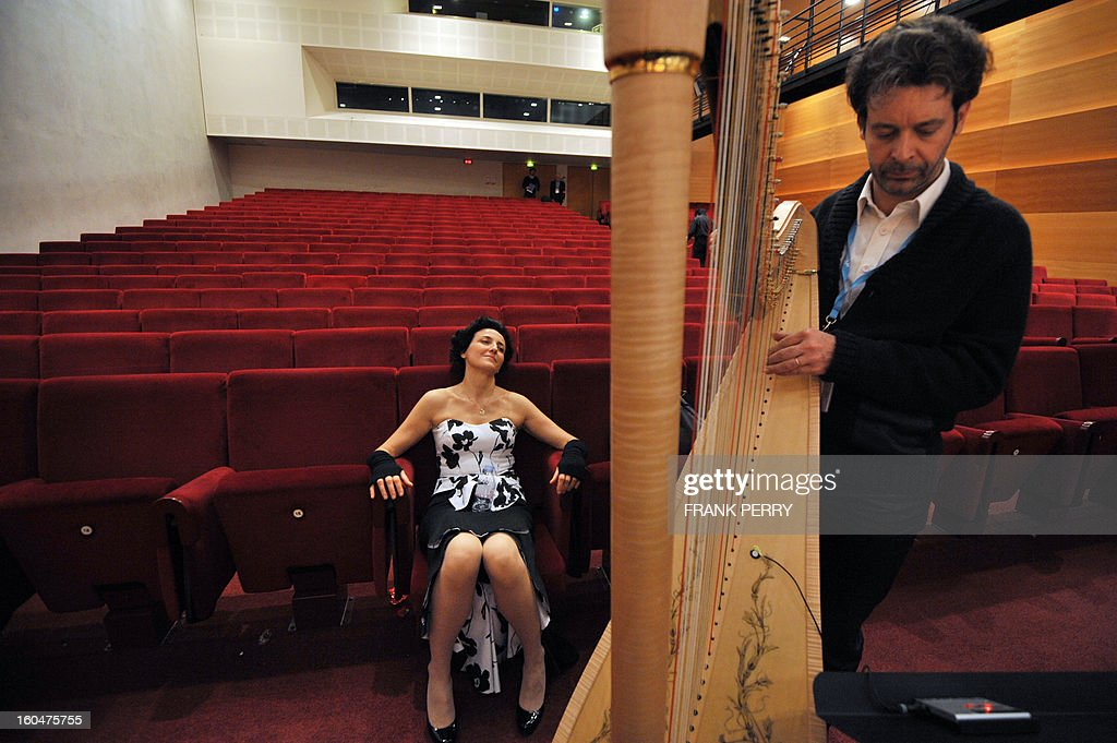 French harpist Isabelle Moretti (L) relaxes prior to a concert with Yokohama Sinfonietta as part of the 'Folle Journee' classic music festival on February 1, 2013 in Nantes. The 19th edition of this festival will run until next February 3.