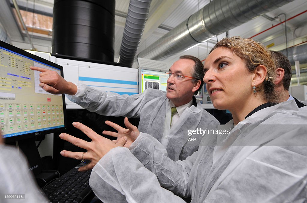French head of MPO Energy Jean Francois Perrin (L), talks to French Ecology Minister, Delphine Batho (R) as she looks at a monitoring screen during a visit of an assembly line of photovoltaic cells at the French MPO Energy plant in Averton, western France, on January 7, 2013.