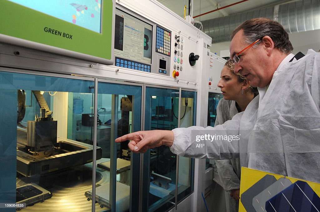 French head of MPO Energy Jean-Francois Perrin (R) shows the company's assembly line of photovoltaic cells to French Ecology Minister, Delphine Batho (L) in Averton, western France, on January 7, 2013.