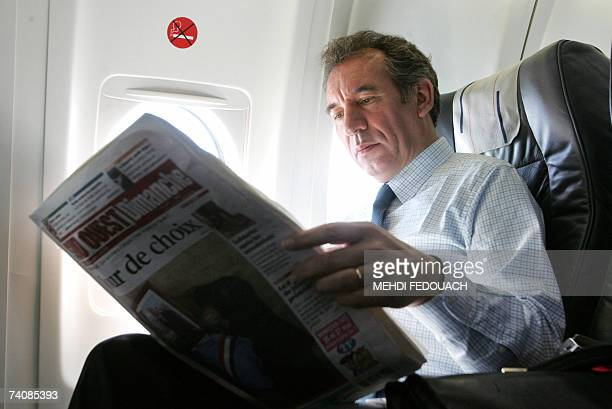 French head of the Union for the French Democracy party Francois Bayrou reads a newspaper aboard a plane en route to Paris 06 May 2007 after voting...
