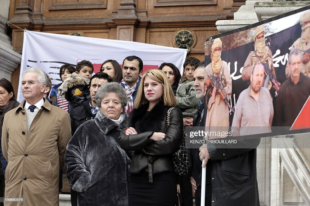 French hostage Philippe Verdon's father, Jean-Pierre Verdon (L) and French Diane Lazarevic, the daughter of French hostage Serge Lazarevic (3rdL) pose with the members of the committee in support to businessman Philippe Verdon and engineer Lazarevic (poster at right), two French hostages in Mali, on November 24, 2012 after a meeting in front of Paris' city hall, to mark the first anniversary of their abduction. Thirteen hostages are held by hardline Islamists in the region which has suffered a devastating collapse since a coup in Bamako in March. Seven of these are French.