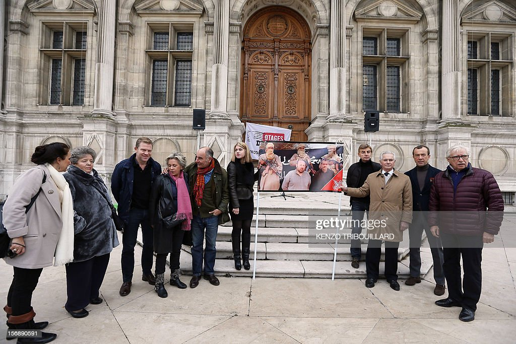French hostage Philippe Verdon's father, Jean-Pierre Verdon (3edR), and French Diane Lazarevic, the daughter of French hostage Serge Lazarevic (6thL) hold a poster of the two French hostages in Mali as they are flanked by French reporter Herve Ghesquiere (3rdL), former hostage in Afghanistan and president of the committee in support to the two men and by Pierre Shapira (R), Paris deputy mayor in charge of Foreign affairson November 24, 2012 after a meeting in front of Paris' city hall, to mark the first anniversary of their abduction. Thirteen hostages are held by hardline Islamists in the region which has suffered a devastating collapse since a coup in Bamako in March. Seven of these are French. AFP PHOTO KENZO TRIBOUILLARD