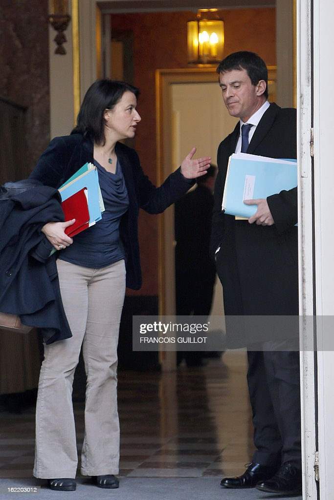 French Housing and Territories equality minister Cecile Duflot (L) talks to French Interior minister Manuel Valls as they leave following a lunch with French Prime Minister and French government's ministers focused on budget on February 20, 2013 at the Hotel Matignon, the Prime Minister official residence, in Paris.