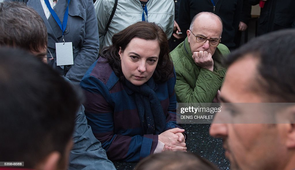 French Housing minister Emmanuelle Cosse (C) and French Interior minister Bernard Cazeneuve (R) speak with Kurdish refugees, on May 30, 2016 during a visit at the Liniere humanitarian camp in Grande-Synthe, northern France. / AFP / DENIS