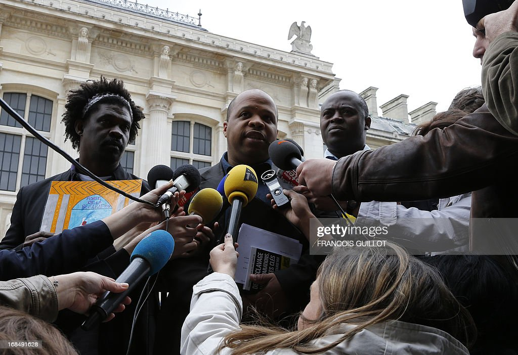 French human rights activist and head of the CRAN (Representative Council of France's Black Associations) Louis-Georges Tin (C) flanked by vice-president Guy-Samuel Nyoumsi (R) and member of the west region CRAN, Jose Jean-Pierre speaks during a press conference outside Paris' courthouse on May 10, 2013. The CRAN announced today it sues the Caisse des Depots for having benefited of slave trade and slavery.