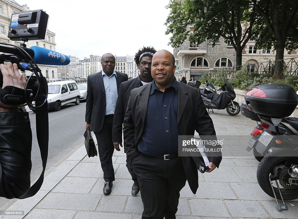 French human rights activist and head of the CRAN (Representative Council of France's Black Associations) Louis-Georges Tin (C) flanked by vice-president Guy-Samuel Nyoumsi (L) and member of the west region CRAN, Jose Jean-Pierre arrives for a press conference outside Paris' courthouse on May 10, 2013. The CRAN announced today it sues the Caisse des Depots for having benefited of slave trade and slavery. AFP PHOTO FRANCOIS GUILLOT