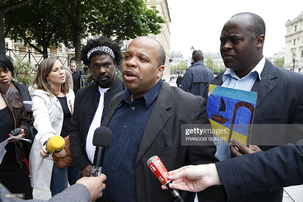 French human rights activist and head of the CRAN (Representative Council of France's Black Associations) Louis-Georges Tin (C) flanked by vice-president Guy-Samuel Nyoumsi (L) and member of the west region CRAN, Jose Jean-Pierre speaks during a press conference outside Paris' courthouse on May 10, 2013. The CRAN announced today it sues the Caisse des Depots for having benefited of slave trade and slavery.