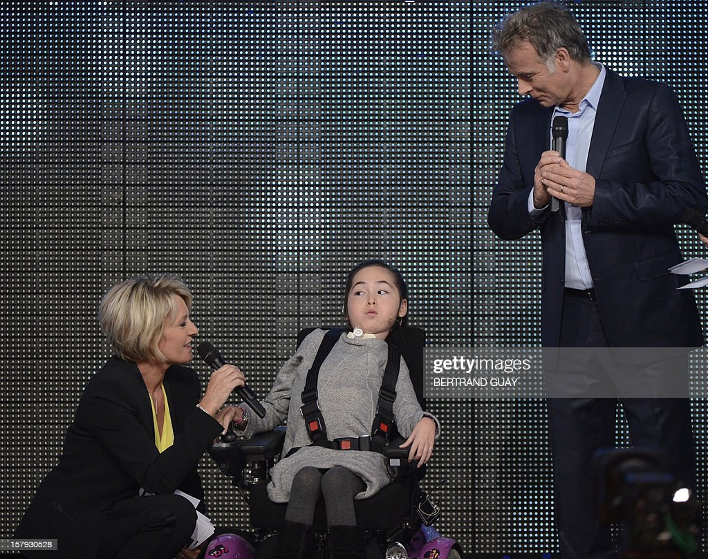 French humorist and godfather Franck Dubosc (R) and French TV host Sophie Davant speak with a child during the 26th Telethon, France's biggest annual fund-raising event during 30 hours of live television transmission, on December 7, 2012 in Saint-Denis, north of Paris. The event, aiming at collecting funds for research on genetic diseases such as myopathy, a neuromuscular disease, will take place on December 7 and 8, 2012. AFP PHOTO / BERTRAND GUAY