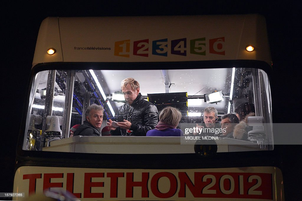 French humorist and godfather Franck Dubosc (L) sits near TV hosts Sophie Davant (C) and Nagui on a bus during a live broadcasting to launch the 26th Telethon, France's biggest annual fund-raising event on December 7, 2012 in Paris. The event, aiming at collecting funds for research on genetic diseases such as myopathy, a neuromuscular disease, will take place on December 7 and 8, 2011.