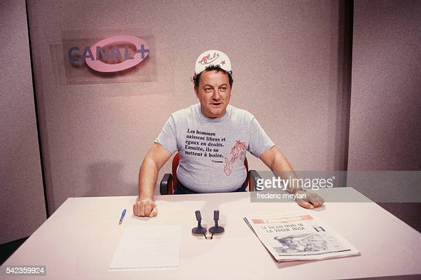 French humorist Coluche on the TV set of Canal Plus where he presents the news in comic form