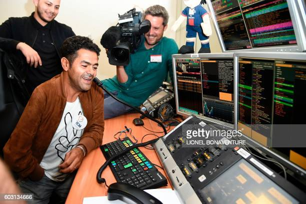French humorist Jamel Debbouze makes a joke with a client of French investment company Aurel BGC while making stock market orders on September 12...
