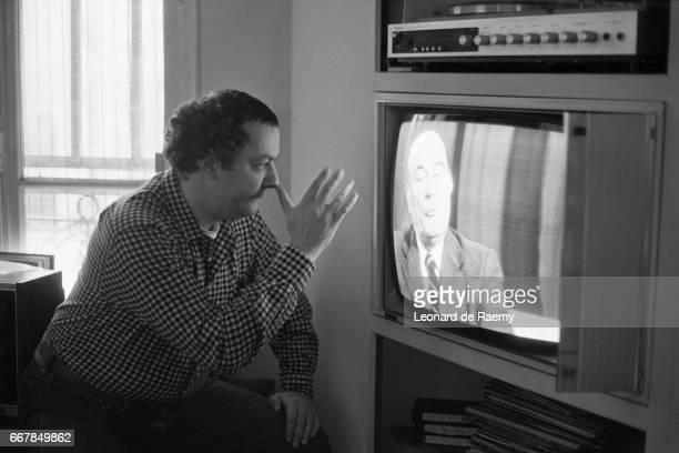 French Humorist Michel 'Coluche' Collucci Watches Francois Mitterrand on TV