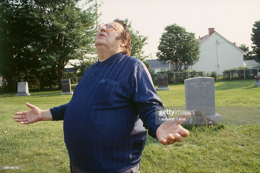 French humorist Raymond Devos during a visit to the grave of Canadian singer Félix Leclerc to film a special television show homage to the singer's...