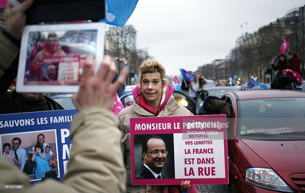 French humorist Virginie Tellene (C), aka 'Frigide Barjot,' holds a poster (translation 'Mister President clean your spectacles, France is in the street') in Paris on February 10, 2013 during a demonstration on the Champs Elysees by predominantly French right wing supporters protesting a proposed law to legalise gay marriage and adoption. France's National Assembly overwhelmingly approved a key piece of legislation that will allow homosexual couples to marry and adopt children, to the delight of gay activists.