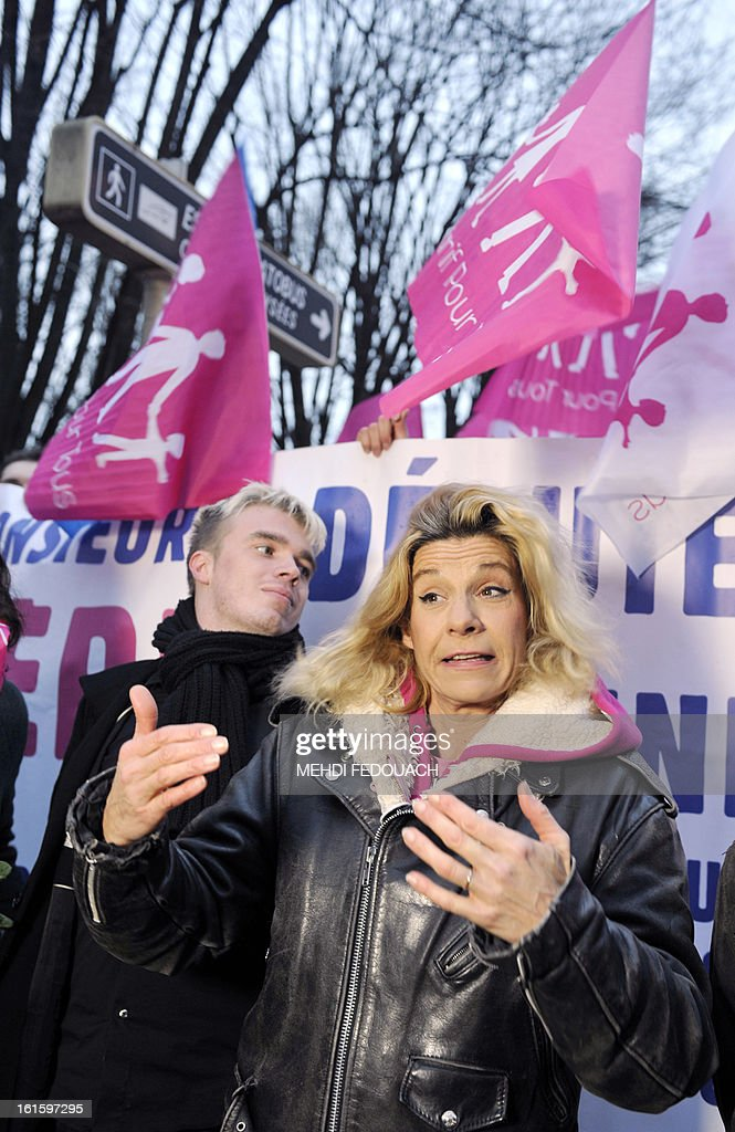 French humorist Virginie Tellene, aka 'Frigide Barjot,' speaks to journalists as she walks with the founder of 'Plus gay sans mariage' association Xavier Bongibault (L) and other activists, toward French National Assembly in Paris, to protest while members of the National Assembly vote on legalising same-sex marriage. France's Parliament examined draft legislation on same-sex marriage after months of rancorous debate and huge street protests by both supporters and opponents.