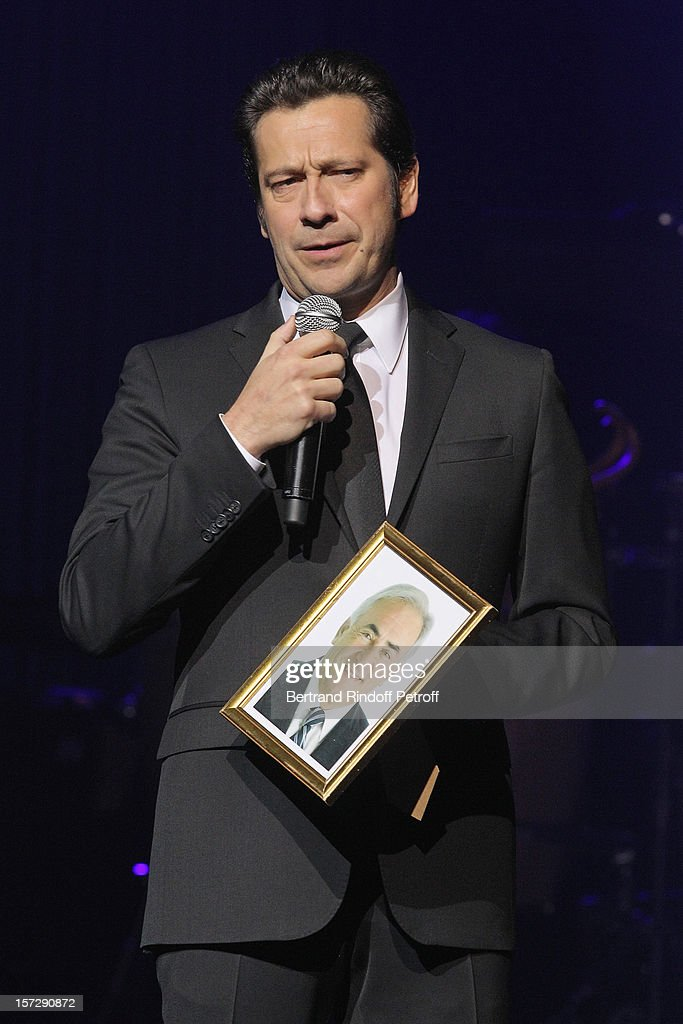 French impersonator Laurent Gerra imitates former French Culture Minister Jack Lang, holding a portrait of former French presidential candidate Dominique Strauss-Kahn, during his One Man Show at Palais des Congres on November 29, 2012 in Paris, France.