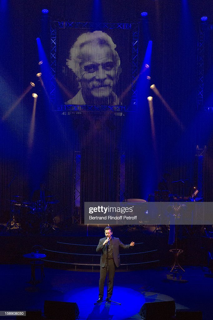 All captions used with this image must detail the personality being impersonated by Laurent Gerra) (FRANCE TABLOIDS OUT) French impersonator Laurent Gerra imitates singer Georges Brassens, whose portrait is displayed in background, during his one man show at Olympia hall on December 28, 2012 in Paris, France.