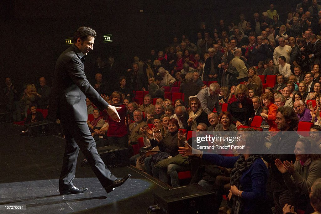 French impersonator Laurent Gerra (L) reaches out to a spectator as he acknowledges applause at the end of his One Man Show at Palais des Congres on November 29, 2012 in Paris, France.