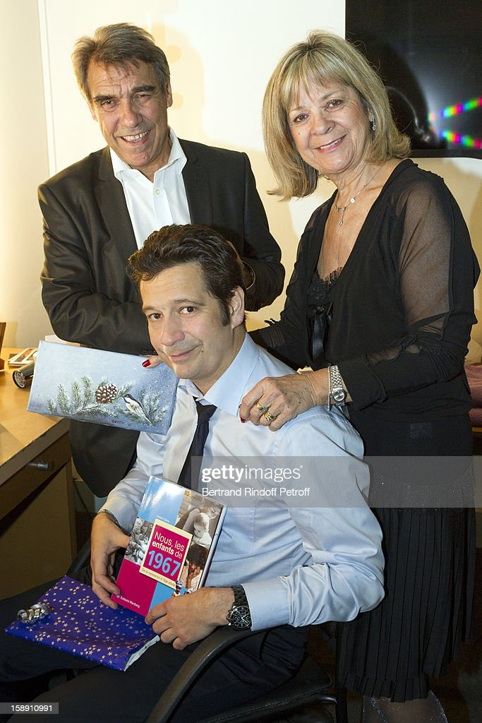 French impersonator Laurent Gerra (C), who turned 45 on December 29, holds some of his birthday presents as he poses with his mother Nicole (R) and father Jean-Christian in his dressing room prior his one man show at Olympia hall on December 29, 2012 in Paris, France.
