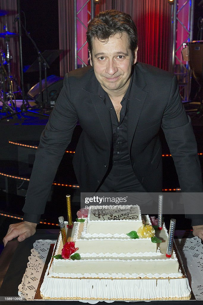 French impersonator Laurent Gerra, who turned 45 on December 29, poses with his birthday cake at the end of his one man show, after he celebrated his birthday on stage, at Olympia hall on December 29, 2012 in Paris, France.