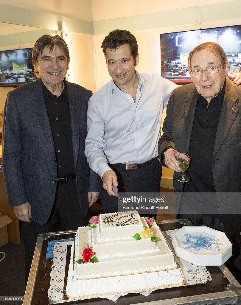 French impersonator Laurent Gerra (C), who turned 45 on December 29, poses with Serge Lama (L) and Robert Hossein, who turned 85 the same day, by his birthday after of his one man show at Olympia hall on December 29, 2012 in Paris, France.