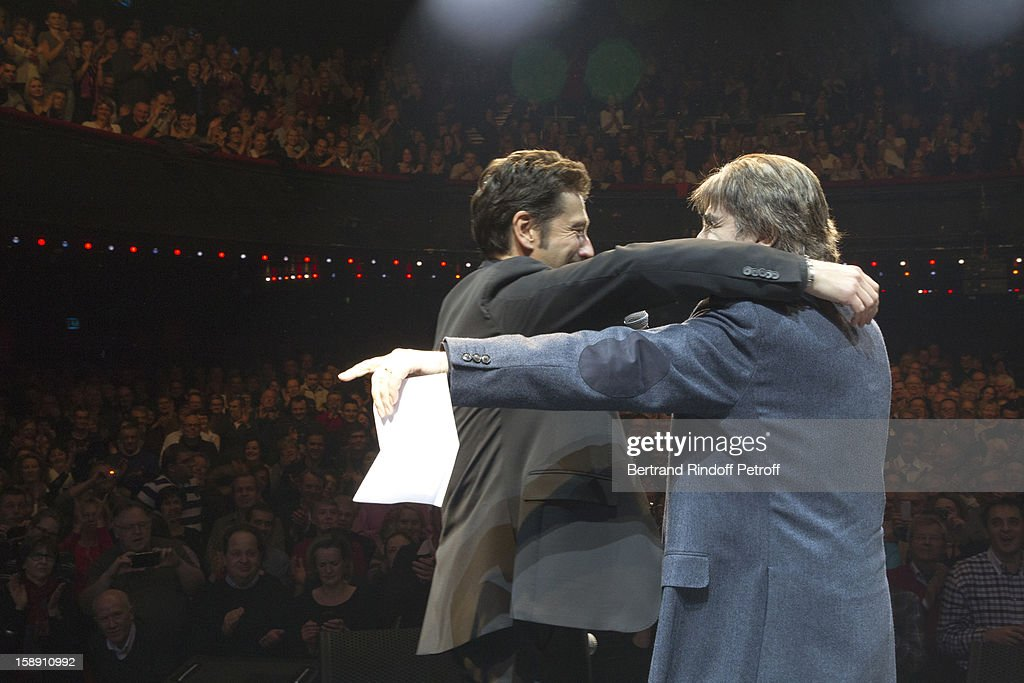 French impersonator Laurent Gerra (L), who turned 45 on December 29, embraces Serge Lama after Lama adressed him a birthday song on stage, at the end of his one man show at Olympia hall on December 29, 2012 in Paris, France.