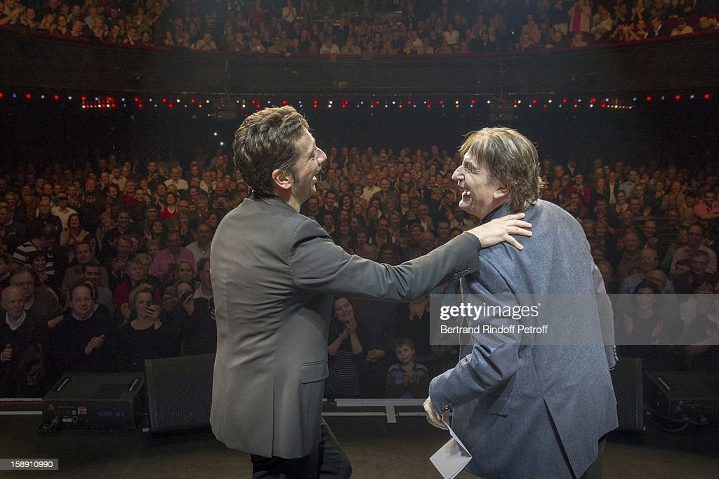 French impersonator Laurent Gerra (L), who turned 45 on December 29, shares a light moment with Serge Lama after Lama adressed him a birthday song on stage, at the end of his one man show at Olympia hall on December 29, 2012 in Paris, France.
