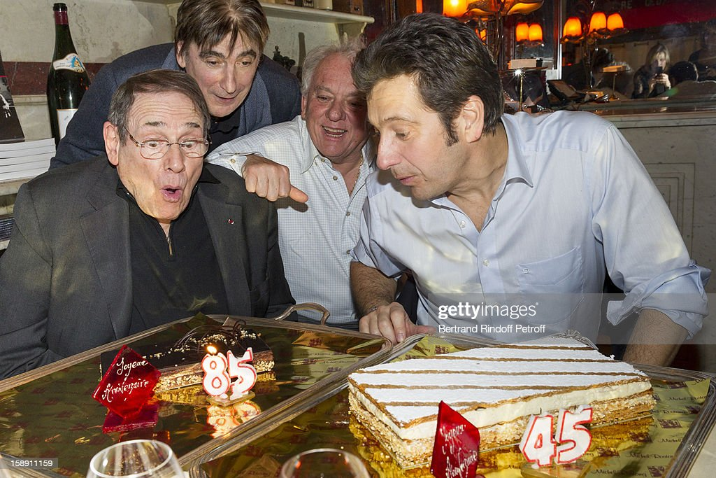 French impersonator Laurent Gerra (R), who turned 45 on December 29, shares a light moment with Robert Hossein (L), who turned 85 the same day, while Serge Lama (2nd L) and Michel Rostang look on, as Gerra and Hossein celebrate their birthday together at Michel Rostang's restaurant 'Le Flaubert, un bistrot d'a cote', after Gerra's one man show at Olympia hall on December 29, 2012 in Paris, France.