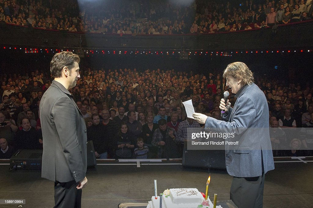 French impersonator Laurent Gerra (L), who turned 45 on December 29, listens to Serge Lama adressing him a birthday song on stage, at the end of his one man show at Olympia hall on December 29, 2012 in Paris, France.