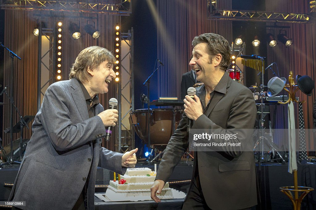 French impersonator Laurent Gerra (R), who turned 45 on December 29, performs with Serge Lama on stage as he celebrates his birthday at the end of his one man show at Olympia hall on December 29, 2012 in Paris, France.