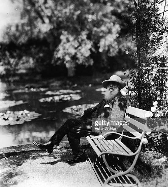 French impressionist painter Claude Monet sits on a bench beside the water lily pond in his home garden Giverny France 1910s