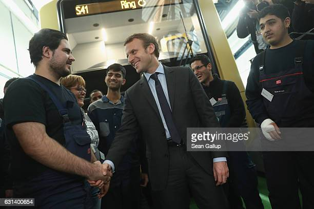 French independent candidate Emmanuel Macron greets participants in a training program for refugees at a train repair facility of German state rail...