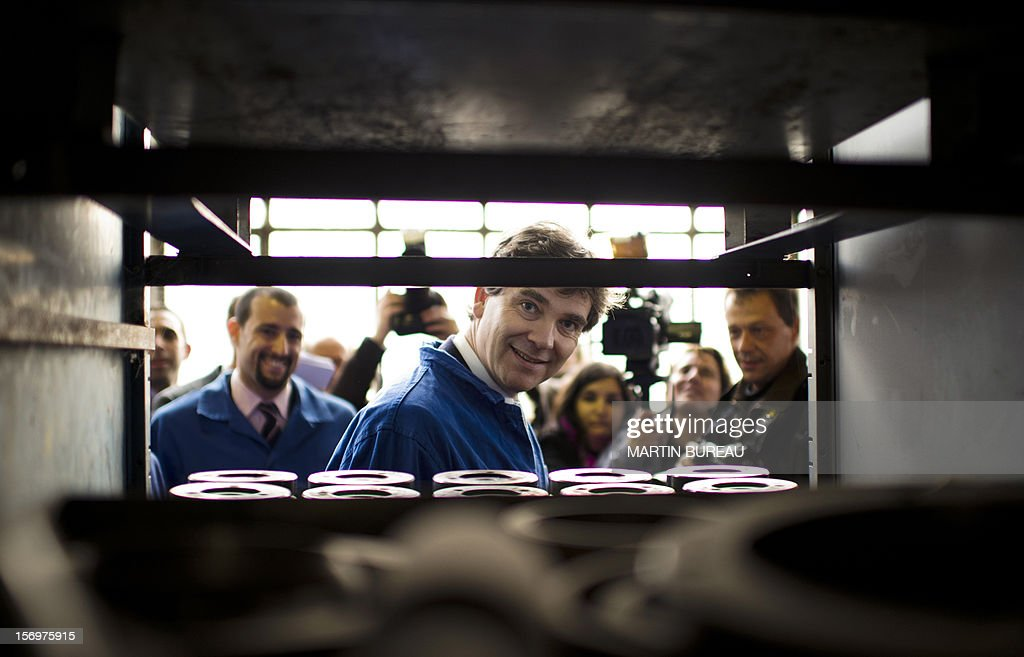 French Industrial Renewal Minister Arnaud Montebourg (C) smiles as he visits the factory of French manufacturer of glassware Duralex, on November 26, 2012 in La Chapelle-Saint-Mesmin. Montebourg does not want steel giant ArcelorMittal in France anymore and is looking for an industrial partner with which to take the group's operations there over on a temporary basis, he said on November 26 in an interview. AFP PHOTO/ MARTIN BUREAU