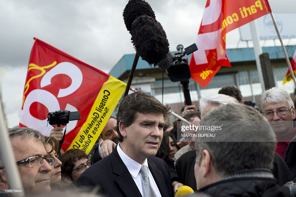 French Industrial Renewal Minister Arnaud Montebourg (C) talks to employees of French manufacturer of glassware Duralex, upon arrival to visit the factory, on November 26, 2012 in La Chapelle-Saint-Mesmin. Montebourg does not want steel giant ArcelorMittal in France anymore and is looking for an industrial partner with which to take the group's operations there over on a temporary basis, he said on November 26 in an interview. AFP PHOTO/ MARTIN BUREAU