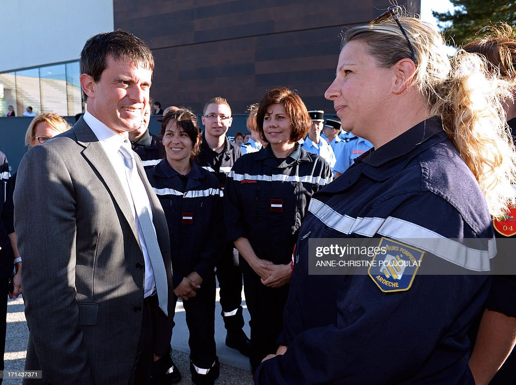 French Interioer Minister Manuel Valls (L) meets firefighter trainees and instructors on June 24, 2013 in the southern French city of Aix-en-Provence during graduation ceremony at the Superior National School of Firefighting Officers (ENSOSP). AFP PHOTO / ANNE-CHRISTINE POUJOULAT