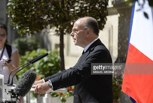 French Interior Minister Bernard Cazeneuve addresses journalists gathered outside the Interior Ministry in the French capital Paris on August 22 2015...