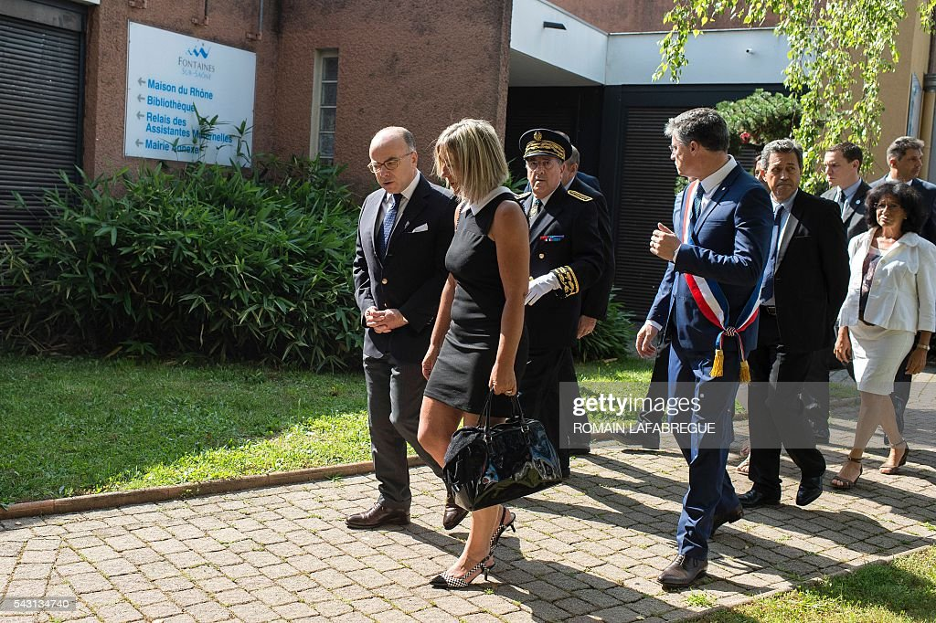 French Interior Minister Bernard Cazeneuve (L) and Herve Cornara's wife Laurence (R), arrive for a memorial ceremony on June 26, 2016 in Fontaines-sur-Saone, in tribute to Herve Cornara, killed one year ago in a terror attack at the Air Products factory in Saint-Quentin-Fallavier. In June, 2015, Yassin Salhi beheaded Herve Cornara, owner of a company where he had worked near Lyon. / AFP / ROMAIN